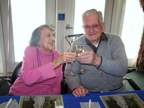 Couple Marjorie and Jackson Reynolds toasting with champagne glasses