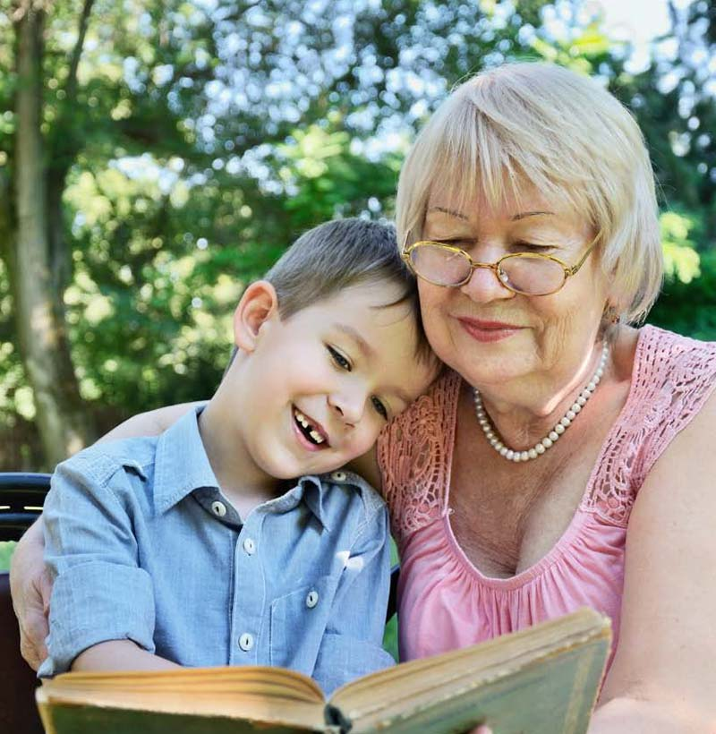 senior woman sitting outside with her grandson, reading him a book