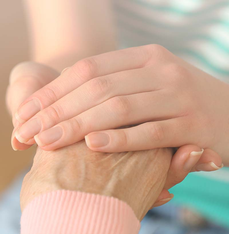 senior holding hands with a caregiver