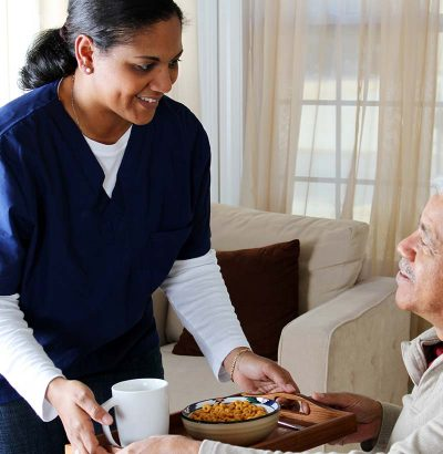 nurse providing senior home care by serving breakfast to a senior man