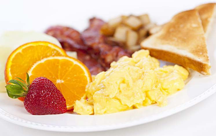 a plate with eggs, bacon, toast, orange slices, and a strawberry