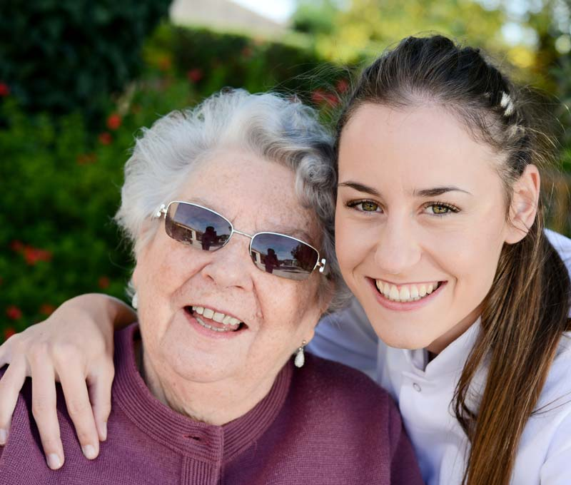 a young female caregiver and a senior woman outside