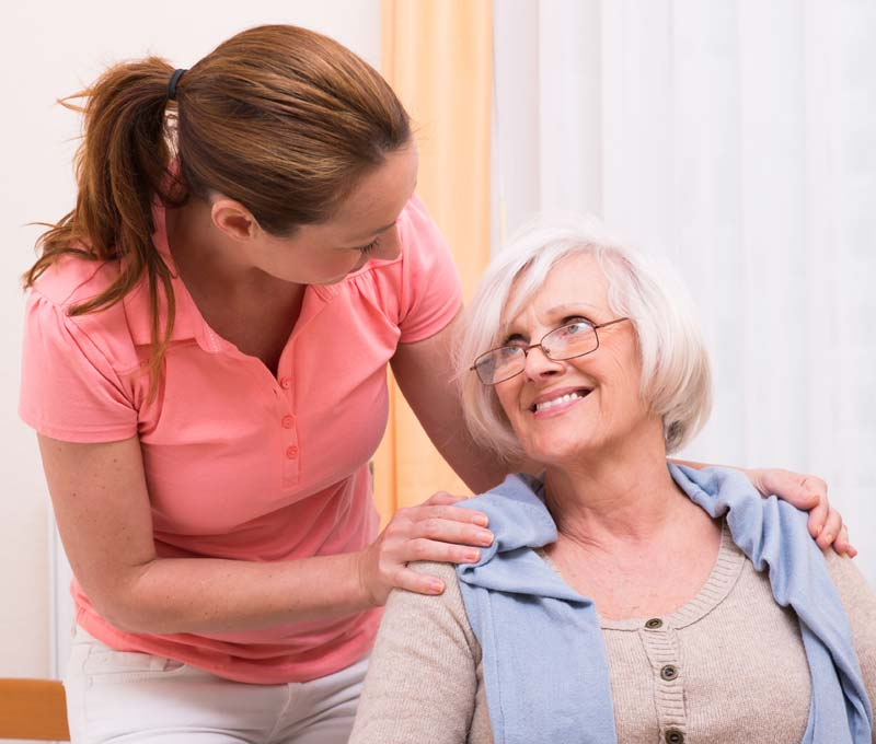 a female caregiver talking to a senior woman with glasses