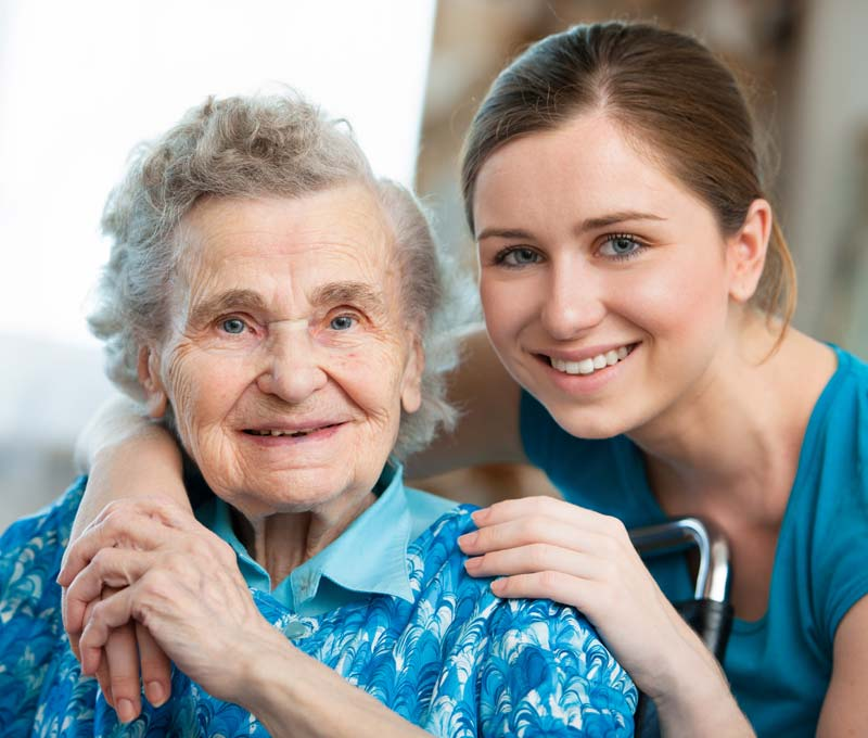 a female staff member at a senior living community holding hands with a senior woman in a wheelchair