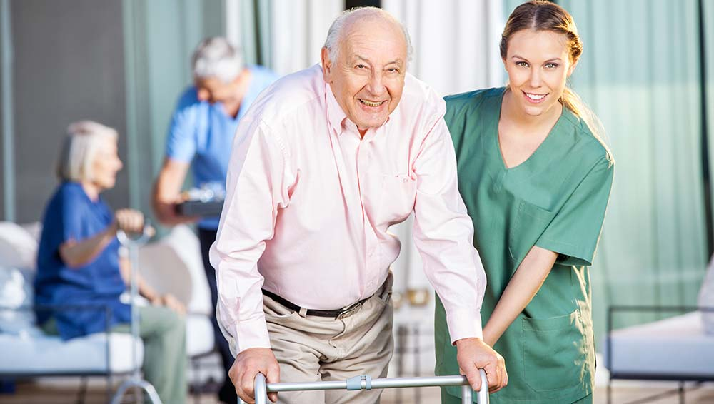 a female nurse who is assisting a senior man who is using a walker