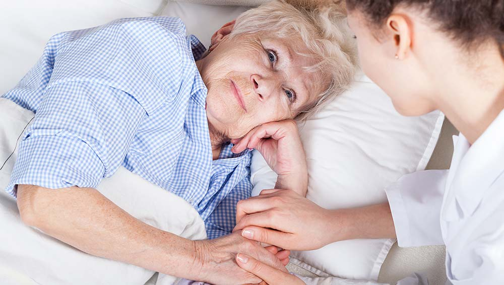 elderly woman being assisted by professional care giver