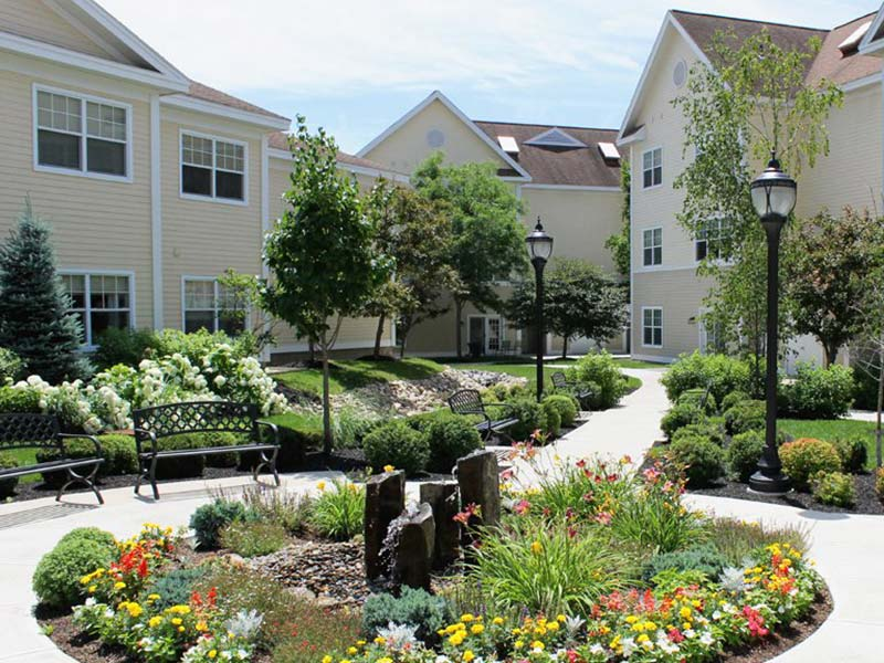 the courtyard of the Woodlawn Commons independent and enriched/assisted living apartments with flowers, benches, and bushes