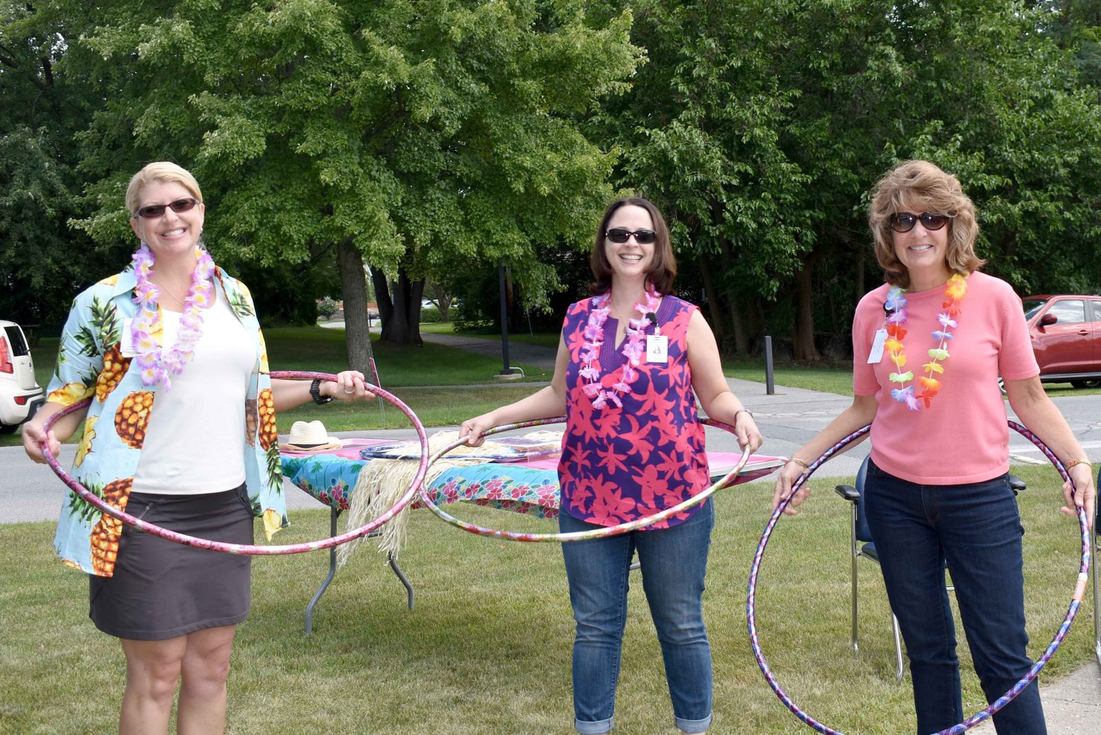 Three employees trying hula hoops at Wesley's employee picnic.