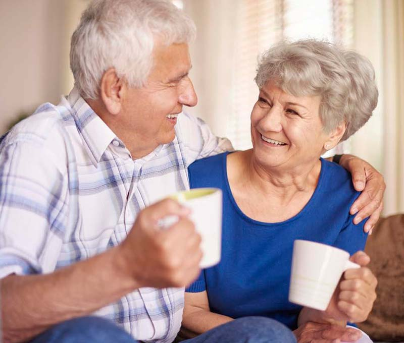 senior man drinking coffee with a senior woman with one arm around her shoulder