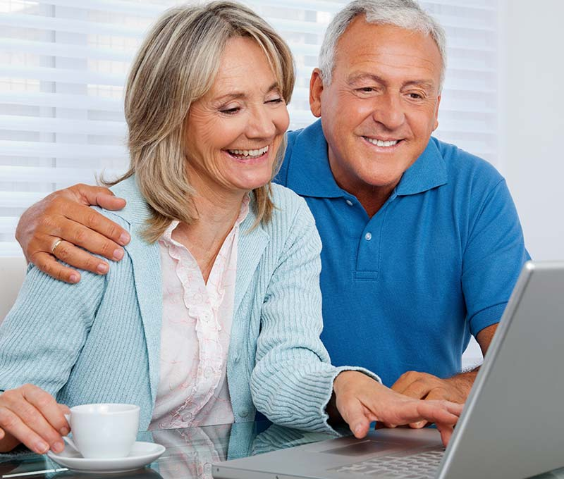 an senior man sitting next to his wife looking something up on a laptop
