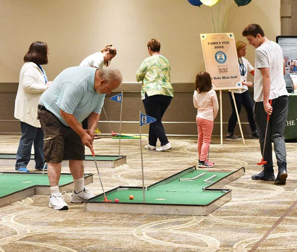 a senior man playing mini golf at the Grandparents Day event