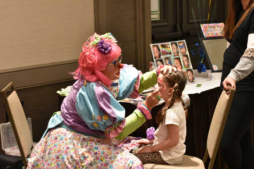 clown painting the face of a young girl at a community event