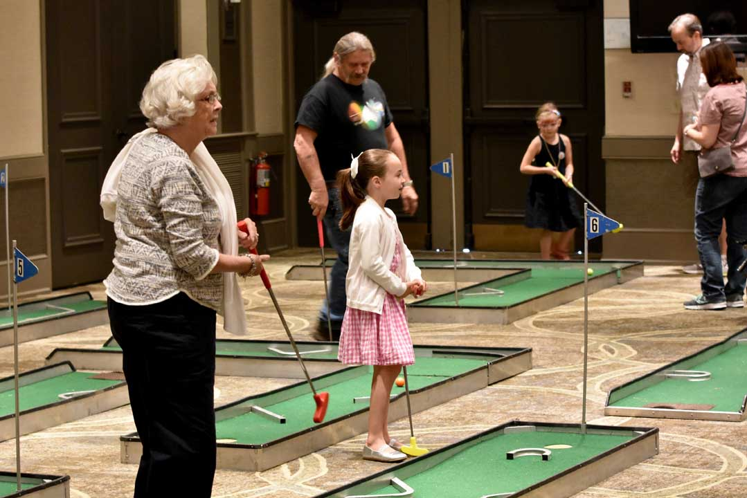 group of people playing indoor mini golf at The Wesley Community's Grandparents Day event