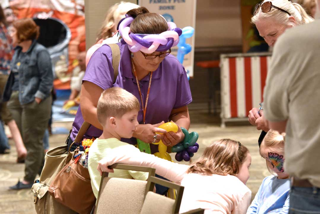 woman making balloon animals for children at a retirement community event