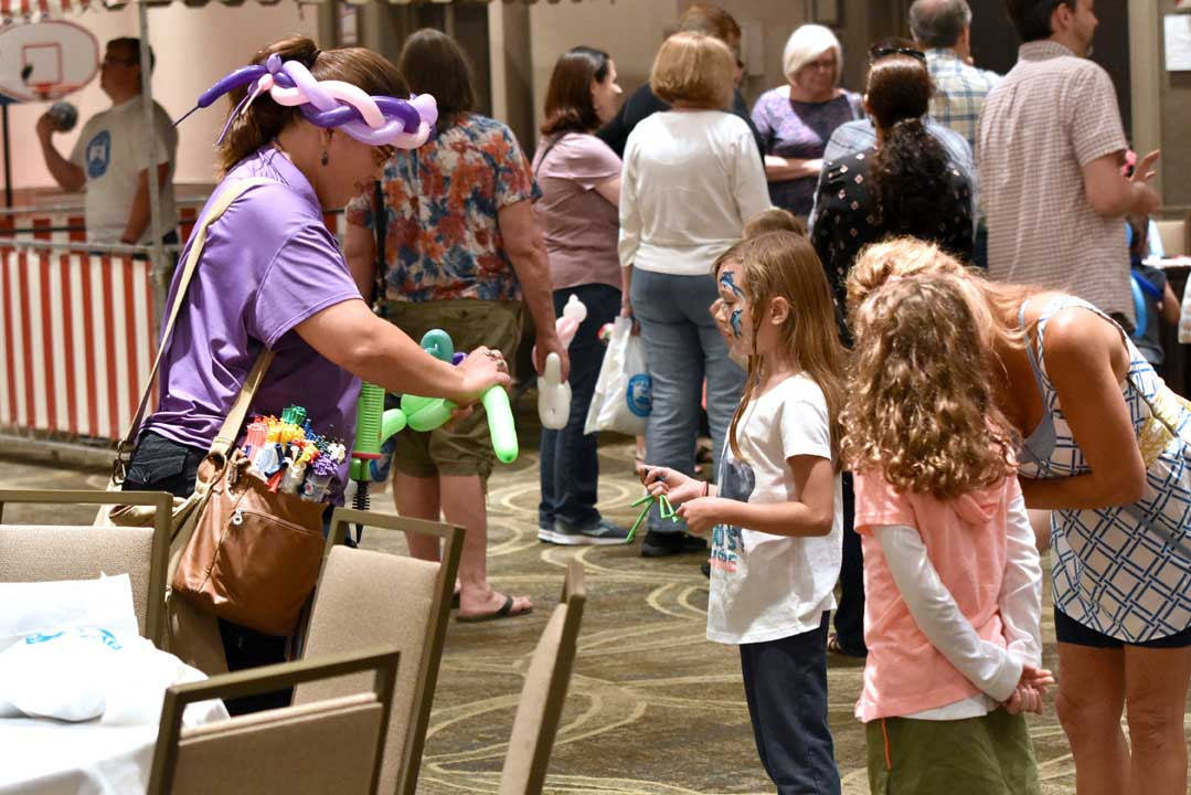 woman making a balloon animal for young girls at Grandparents Day event