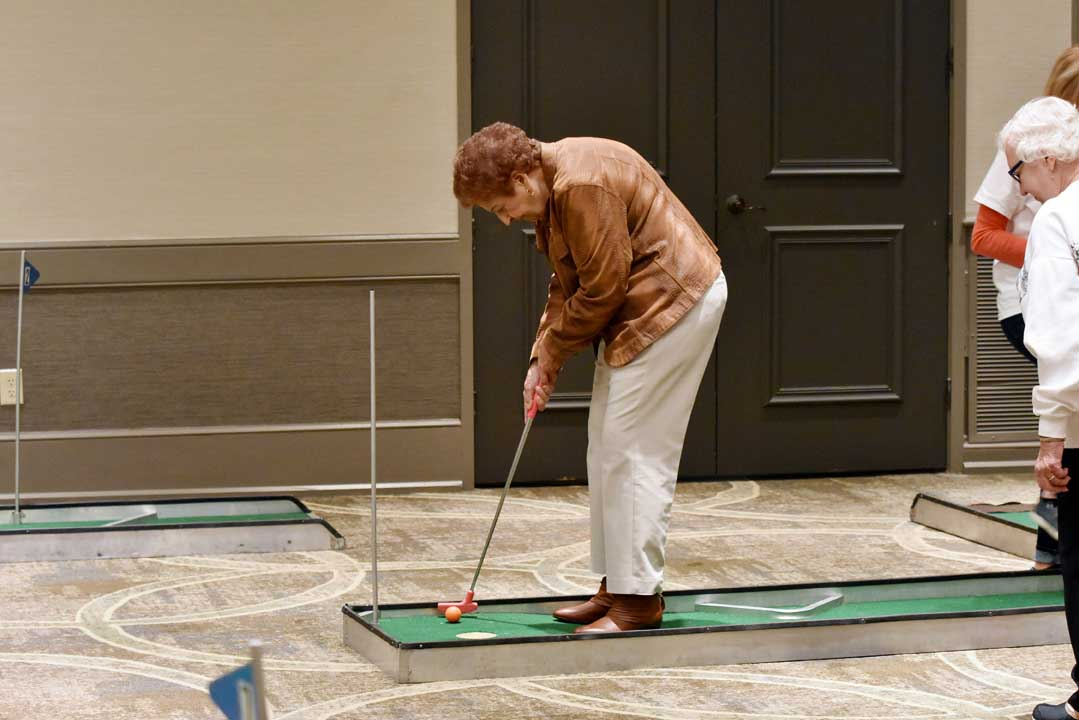 senior woman playing mini golf during an event at The Wesley Community
