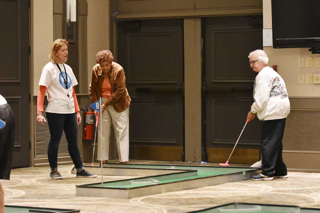senior women playing miniature golf during retirement community event