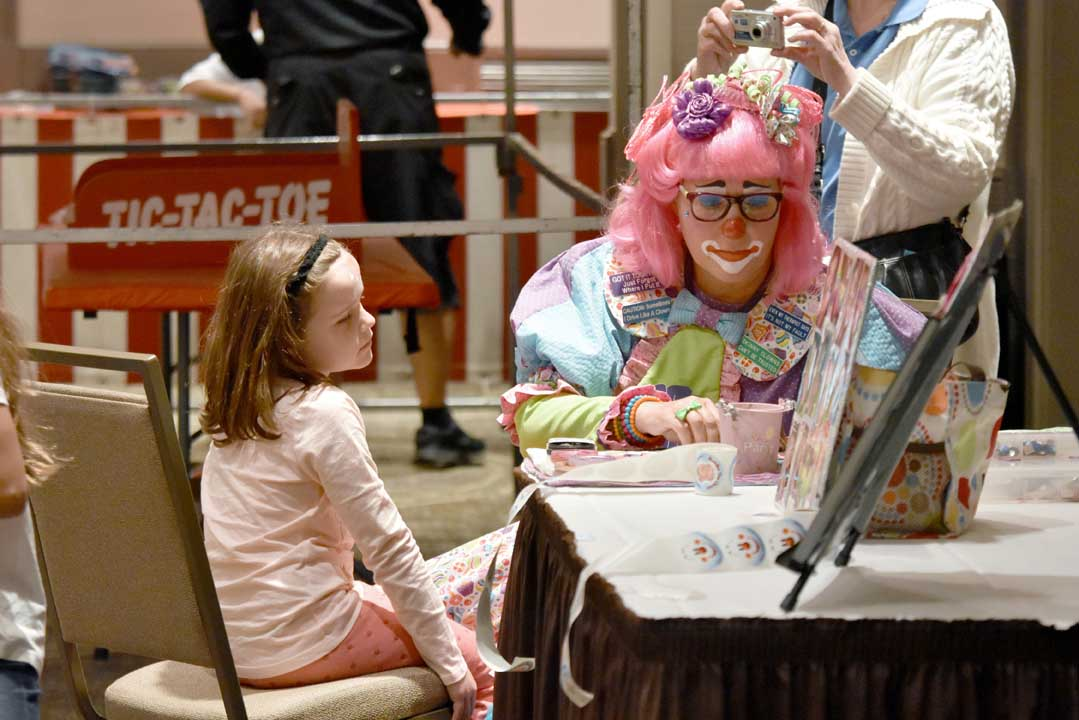 clown face painting a girl during Grandparents Day event