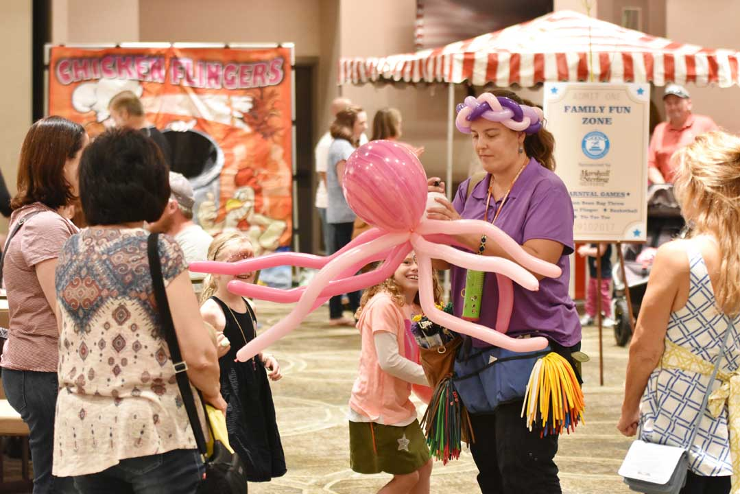 woman wearing a balloon hat and making an octopus out of balloons