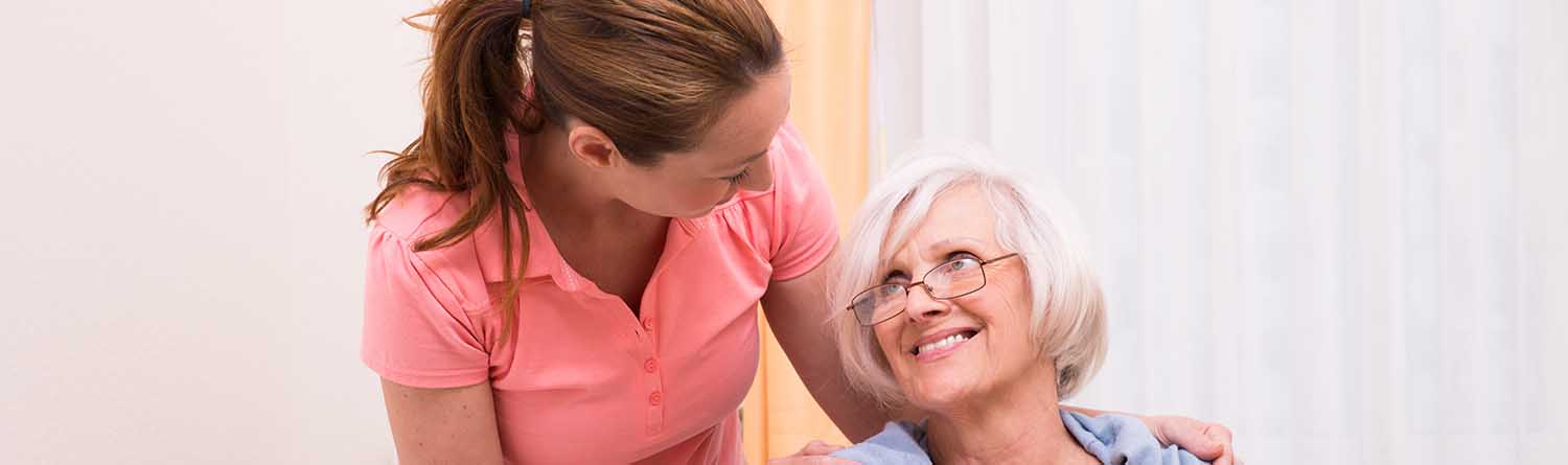 close-up of a female caregiver with her hands on the shoulders of an elderly woman