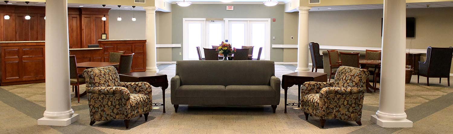 a reception area with chairs, tables, and couches at the Woodlawn Commons enriched/assisted living community