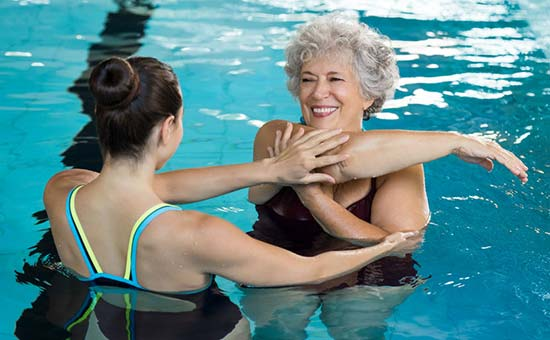 an aqua aerobics trainer helping a senior woman exercise in a pool