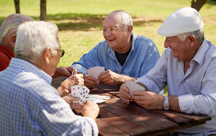 senior men playing cards at a picnic table
