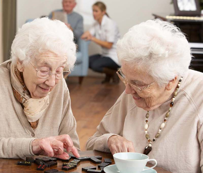 two senior woman playing dominoes