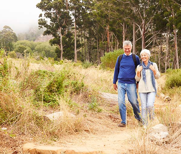 an elderly man walking on a hiking trail with his wife