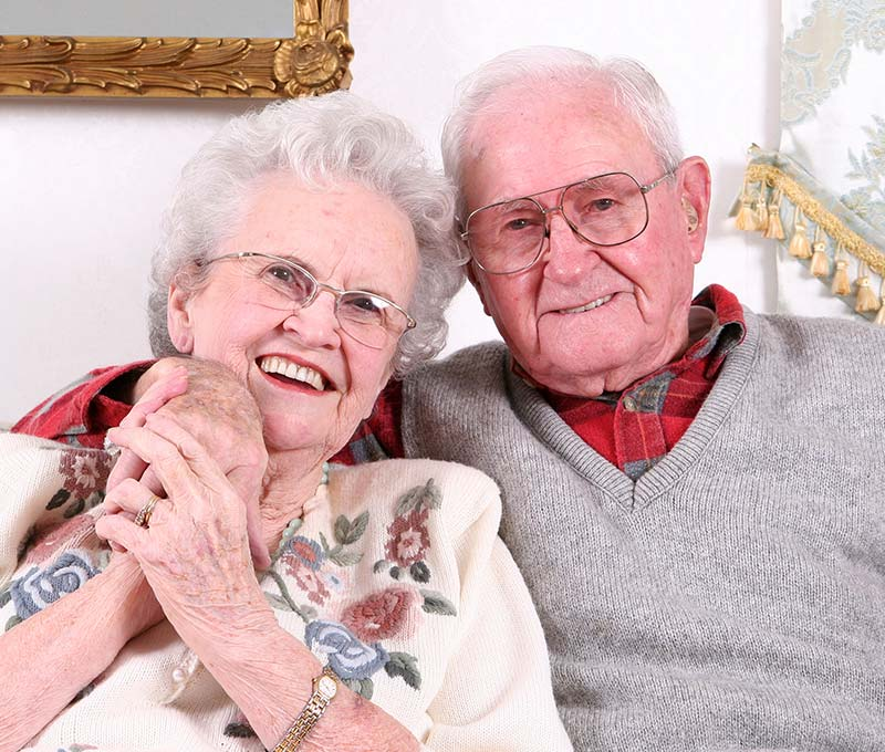 a senior man with his arm around a senior woman