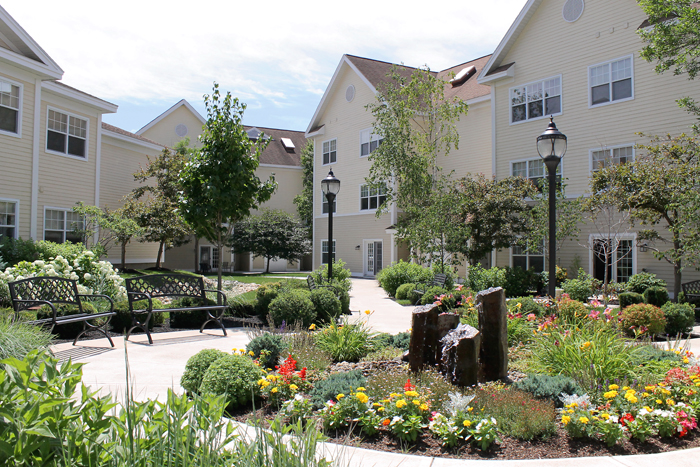 water fountain, landscaping, benches and walkways outside of the Woodlawn Commons retirement community