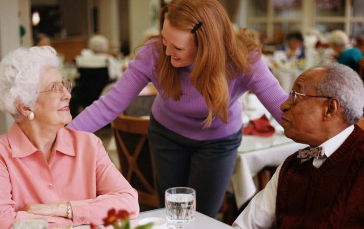 female caregiver talking to a senior woman and a senior man who are sitting at a dinner table