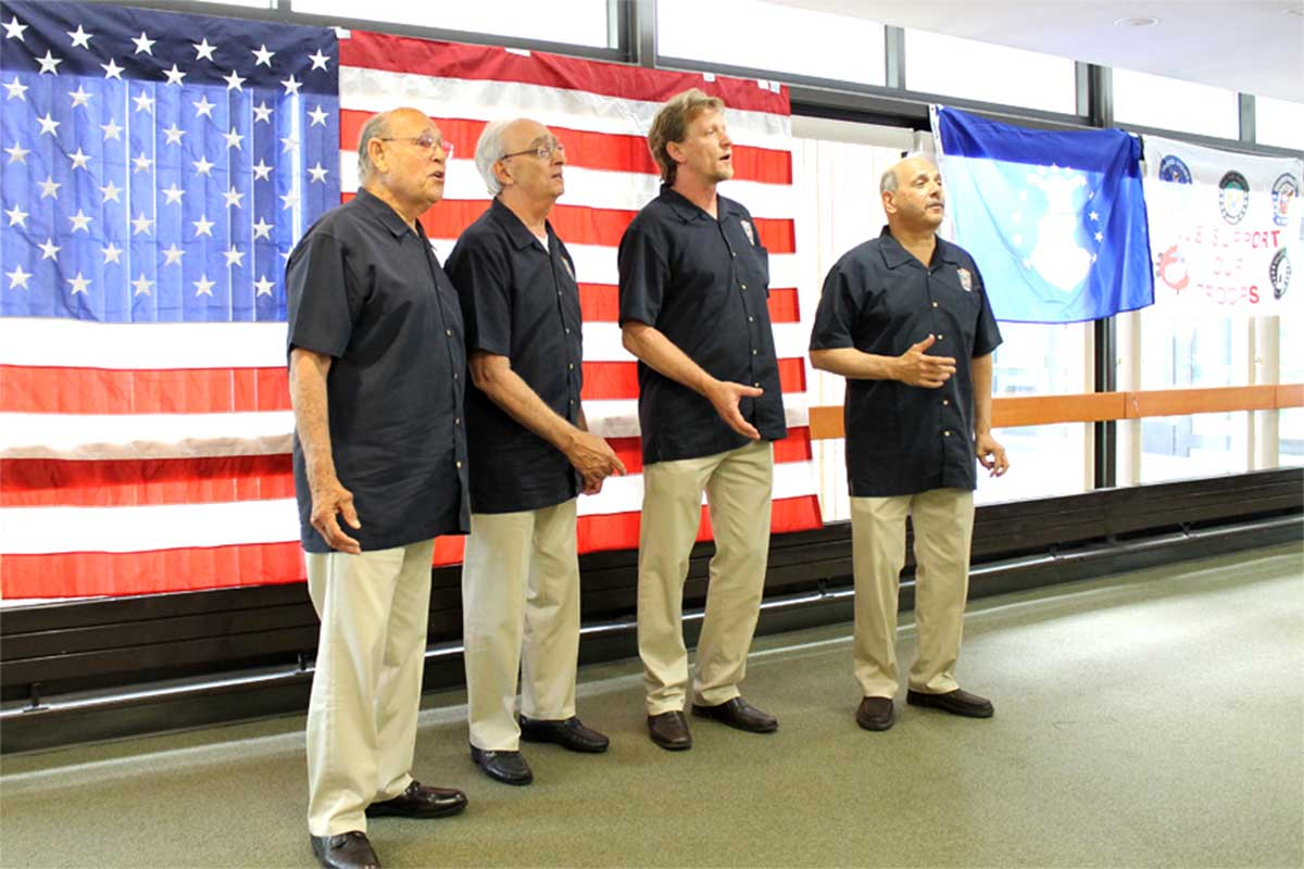 4 men singing in front of US flag