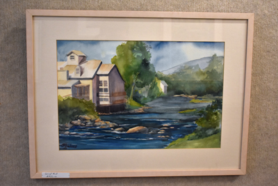 Framed painting of a house on the water