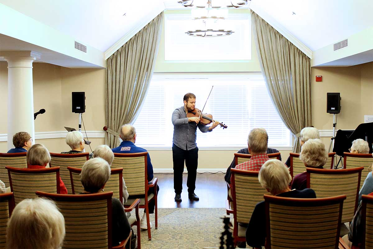 Man playing violin for group