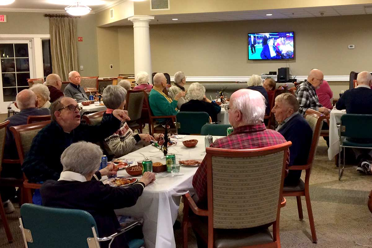 Seniors gathered in large room watching TV