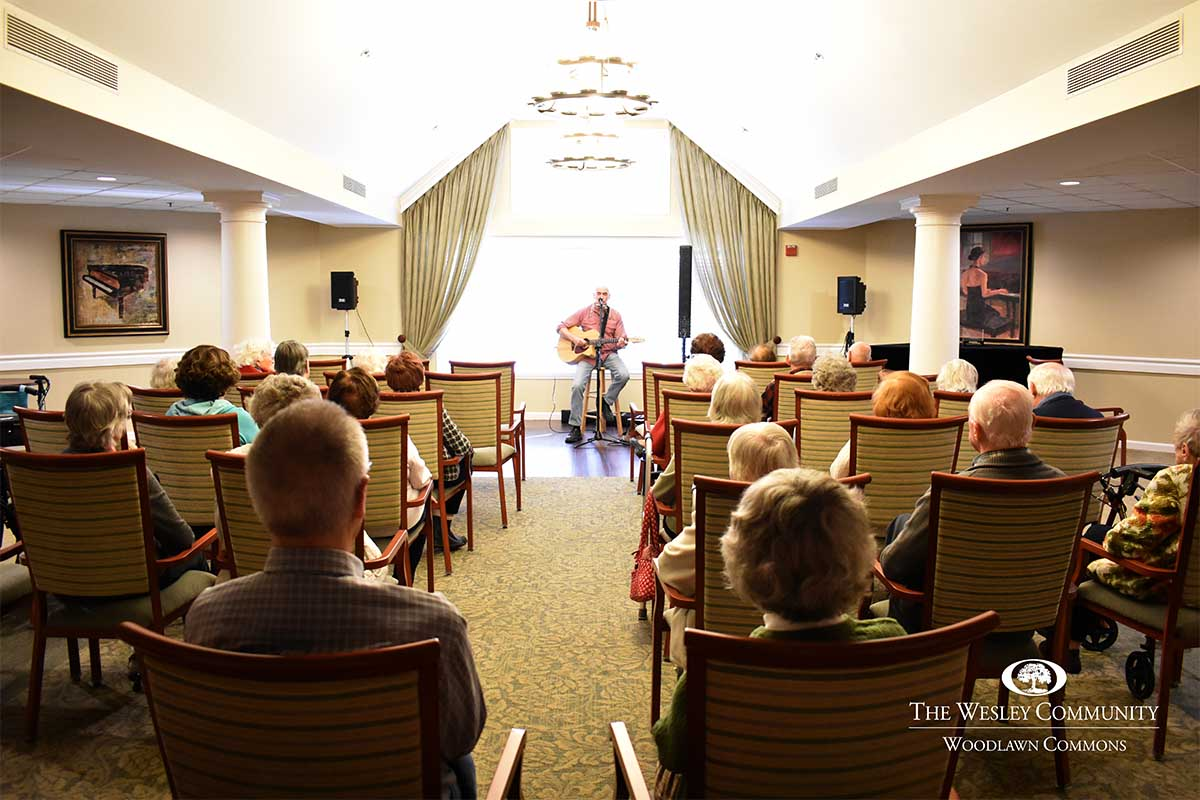 man performing in front of seniors with guitar