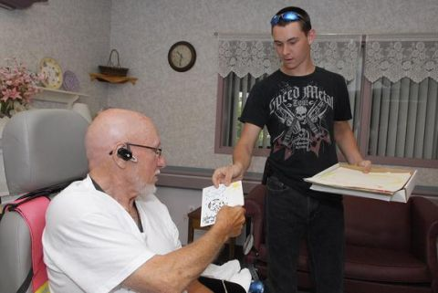 BOCES student handing a gift to a resident