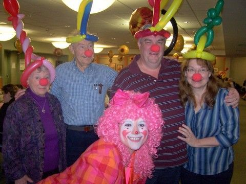 Group of 4 residents dressed up as clowns with balloon hats and red noses on with a clown in front of them