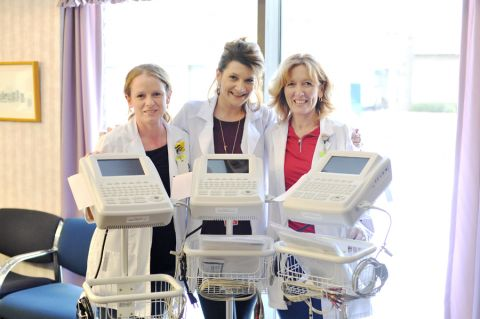 Three women from the Health Care Center standing behind three newly bought machines