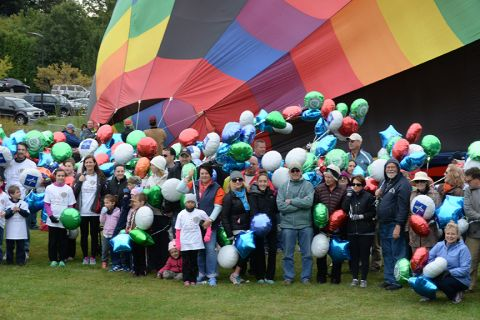 Large crowd holding balloons standing in front of a hot air balloon