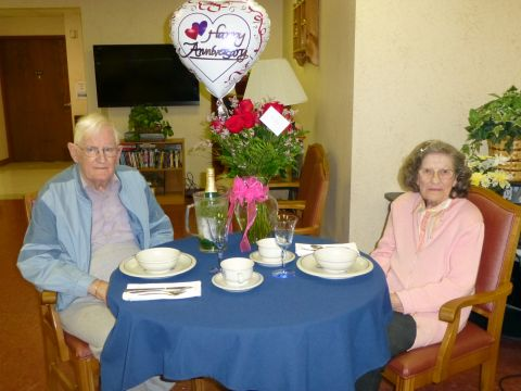 Omar and Gloria Herrick sitting at a table with a Happy Anniversary balloon on it