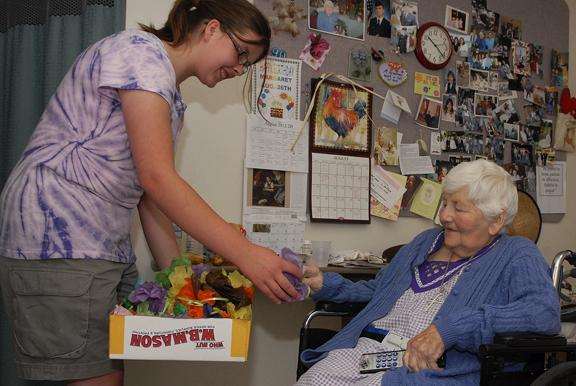 Student Michelle Keefe handing Margaret Labish resident a gift