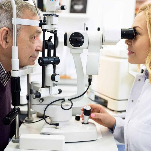 Female ophthalmic doctor check eyes to elderly man in eye clinic