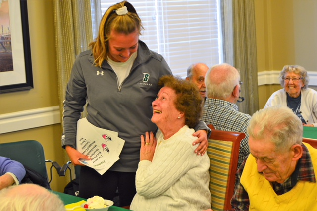 Siena lacrosse player Diana Bradbury laughing with her arm around Woodlawn Commons resident Connie Bassani