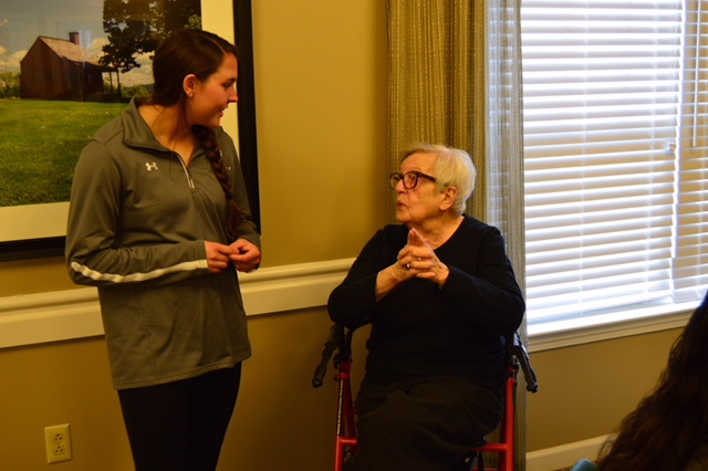 Woodlawn Commons resident Lee Nelson talking with with Siena women's lacrosse player Annie Brennan