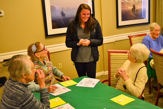 Siena women's lacrosse player Julia Sardella talking to a group of senior residents at a table