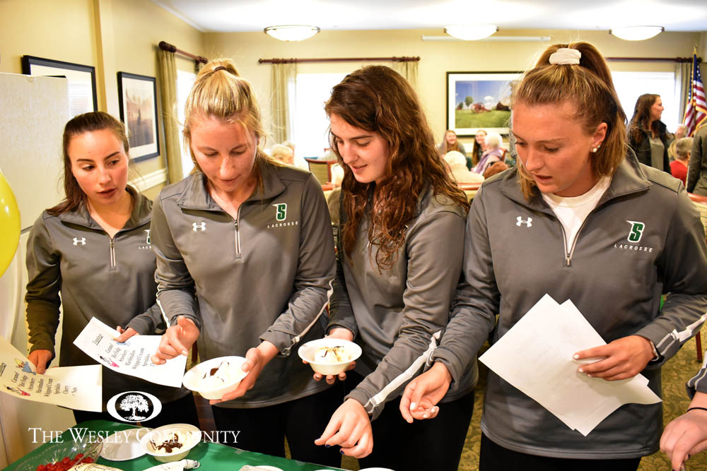 Sienna women's lacrosse players make sundaes for Woodlawn Commons residents.