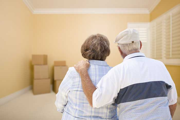 Hugging Senior Couple In Room Looking at Moving Boxes on the Floor.