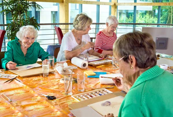 Group of four female cheerful older students painting together at table in spacious room with large windows.